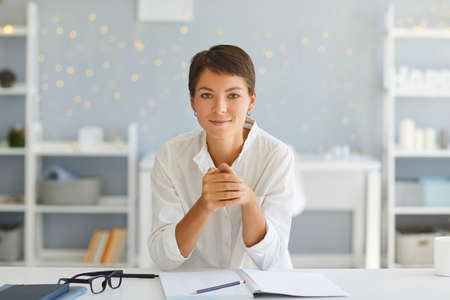 Portrait of confident happy young lady, professional coach, course author, successful business woman or female psychologist, sitting in her home office at desk with open notebook looking at camera