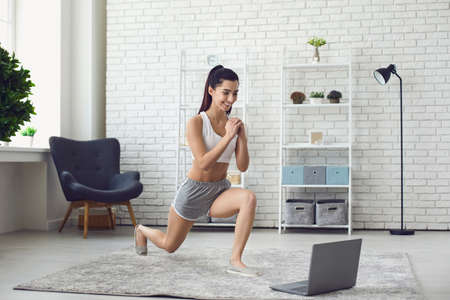 Young smiling slim girl in sports clothing doing morning sports workout during online lesson on laptop at home. Online fitness practice concept