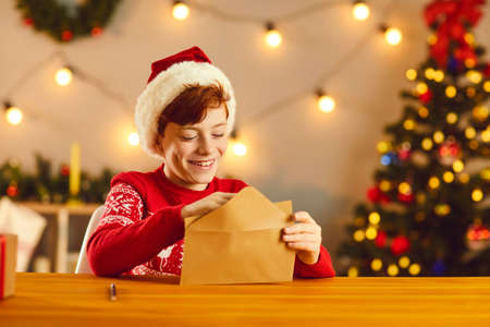Happy smiling child putting his letter and wish list in a craft paper envelope before sending it to Santa Claus by mail. Christmas traditions, hope, believing in magic, joy and holiday spirit concept Фото со стока