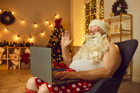 Santa Claus in underwear sitting in armchair and waving hand at laptop computer screen starting online video call. Concept of self-isolation at home, virtual Christmas celebration and staying in touch Фото со стока