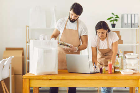 Employees of a healthy food restaurant record data and pack food containers for delivery to their customers. Man and woman pack food in white bags and work with a laptop.