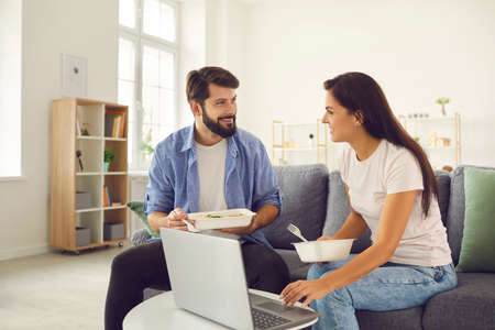 Cheerful young couple eating food from delivery sitting in front of laptop talking and discussing movie. Man and woman have fun at home during the weekend.