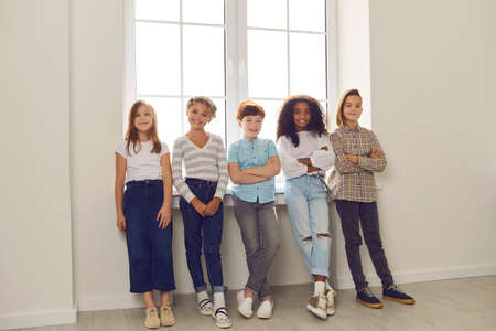 Group of happy diverse friends standing by the window, looking at camera and smiling in new home or during break at school or educational center. Childrens development, intercultural kids community