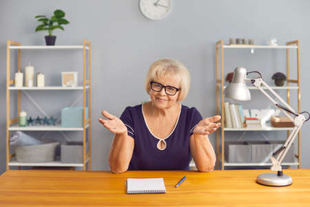 Portrait of happy mature woman in glasses and casual wear sitting at desk with notepad and pen, gesturing and looking at camera as if talking and attentively listening to interlocutor on video chat
