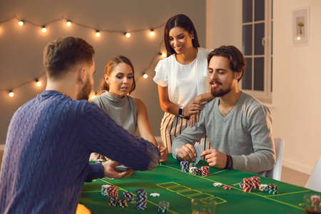 Gambling, casino at home, board games, playing cards concept. Group of young friends awaiting for card from deck during betting and playing poker on table at home with decorated room interior