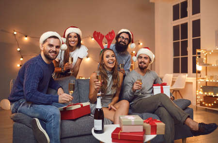 Portrait of a group of friends in Santa Claus hats and with glasses of champagne in their hands exchanging gifts and celebrating the New Year. Concept of celebrating Christmas and New Year at home.