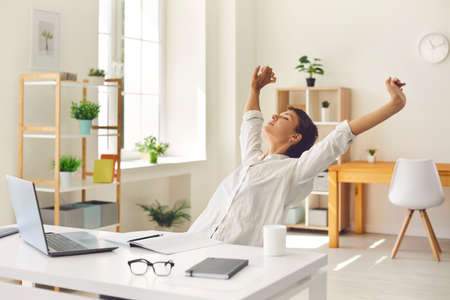 Happy young business woman sitting at office desk with eyes closed, stretching arms and back trying to relax stiff, tense muscles, enjoying break during working day