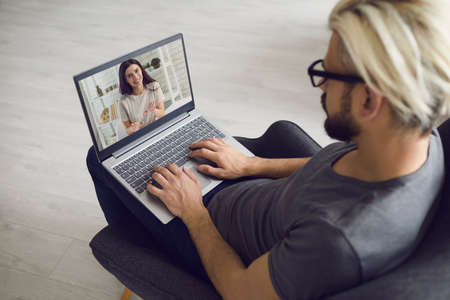 Young man freelancer is at home, sits in a chair and communicates online with a woman. A young woman on a laptop eran uses a video call and video chat. Working online, remote communication. Video conference online.