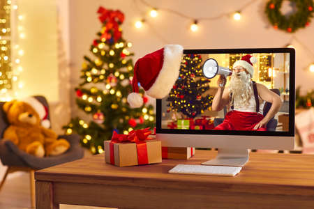 Desktop computer showing online ad with funny Santa Claus yelling in megaphone announcing the start of big New Year and Christmas sales and discounts, promising amazing deals, gifts and presents Фото со стока