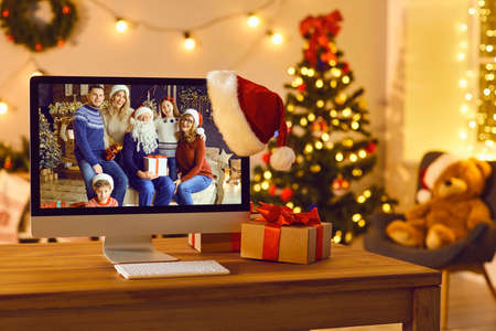 Getting together with your loving family is the best gift. Computer with photo of happy parents and children reunited for Christmas set as desktop background standing on desk in cozy room Фото со стока