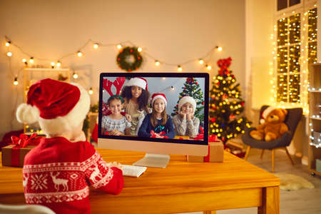 Kids video calling each other to stay in touch on winter break. Little boy in Santa hat sitting in front of computer screen, chatting online with group of his diverse friends on Christmas Eve at home Фото со стока