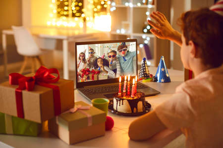 Birthday online. Children remotely wish their friend happy birthday using video call chat conference laptop. Фото со стока
