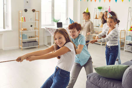 Team of happy diverse children in funny hats playing tug-of-war at birthday party at home. Group of smiling kids having fun and enjoying interesting games in after school leisure club or center Фото со стока