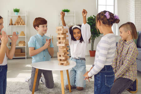 Hooray, I did it! African American girl raised her hands up rejoicing that she had won this round in a game of jenga. Kids playing board game with wooden bars while sitting around a table in the room.