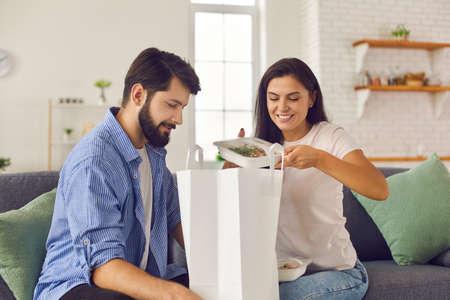 Young couple taking healthy food in boxes and drinks out of paper bags delivered by food service to apartment. Healthy food delivery service and daily ration concept