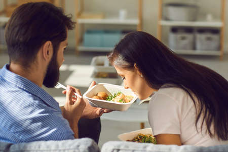 Two young people eating fresh natural healthy takeaway meals from containers that they ordered in express food delivery service. Woman smelling boyfriends salad while having lunch together at home