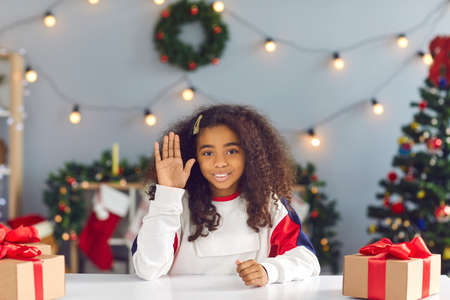 Christmas background. Cute african american schoolgirl with curly hair sits at a table with gifts in front of a webcam and waves a hand greeting friends in video chat. Video meeting concept