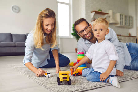 Portrait of a little boy playing with toy cars with his parents sitting on the carpet on the floor. Mom, dad and kid in playroom. Family leisure time. Childhood and playing concept. Фото со стока