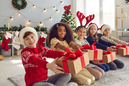 Group of smiling children in Santa hats and reindeer antlers sitting in row holding presents, willing to share joy, kindness and holiday spirit and wishing everyone Merry Christmas and Happy New Year
