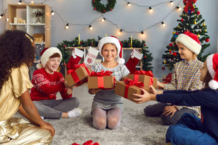Group of generous diverse children giving presents to their friend or sister sitting on floor in cozy living-room on Christmas morning. Happy girl getting lots of New Year gifts from smiling friends Фото со стока