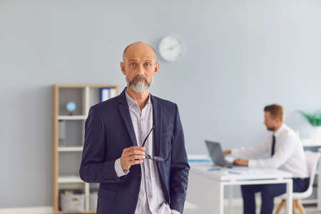 Serious mature male company executive standing in office with subordinate working in background. Portrait of sceptical bald bearded old business owner holding eyeglasses looking at camera Фото со стока