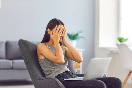 Young tired dissatisfied worried business woman sitting in a chair with a laptop in a bright office. Woman covers her face with her hands from fatigue. Business problem concept.
