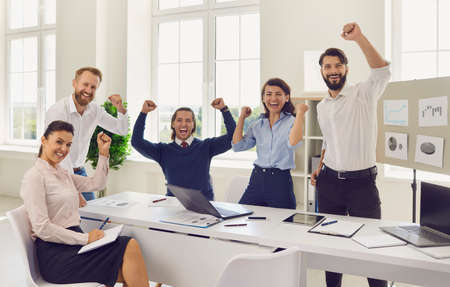 Happy Sales Department team celebrating corporate victory, achieving good results and increasing sales. Excited employees cheering during successful meeting in company boardroom