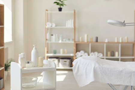 Body care. Interior of professional spa salon or dermatology room with all necessary supplies. New massage room with empty bed with fresh white cover, and organic skincare products ready for use