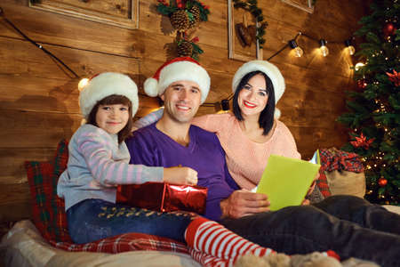 Happy family is reading a book while sitting on a bed in a room in Christmas. Фото со стока