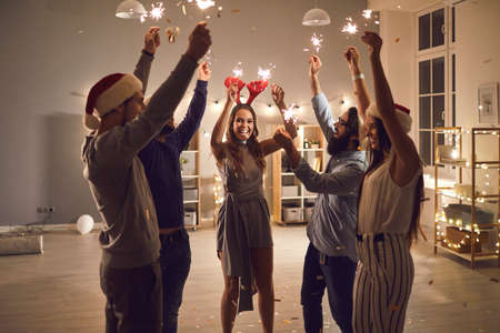 Group of smiling young friends or coworkers holding burning sparklers and wishing each other Merry Christmas and Happy New Year at cozy party at home or in company office decorated with lights.