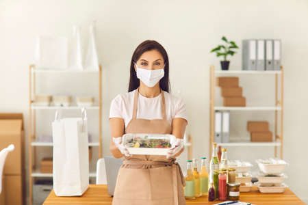 Takeaway cafe worker wearing face covering mask holding fresh healthy lunch in plastic food container ready to be delivered to client. Safe meal delivery service and taking care of customers concept Stockfoto