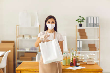 Responsible takeaway cafe worker in face covering mask and gloves holding paper bag with fresh lunch ready to be delivered to client. Safe meal delivery service and taking care of customers concept