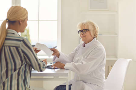 Friendly senior female doctor gives a prescription to a patient in his office. Healthcare in a modern hospital or private clinic. Concept of disease prevention and consultations in the medical office.