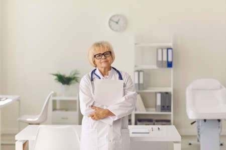 Portrait of a stylish senior female doctor with documents in her hands, who is dressed in a white coat and stands in a modern hospital room. Healthcare and medical concept. Фото со стока
