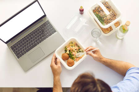 Top view of cropped busy worker sitting at office desk with laptop computer with blank white mockup copyspace screen, enjoying lunch break and eating healthy meal ordered on food delivery website