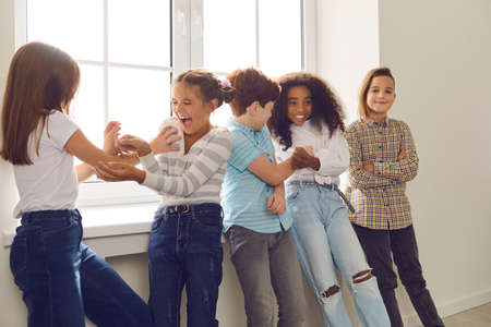 Active group of multiethnic children have fun together and tickle each other standing by a large window in a bright room. Concept of positive emotions.