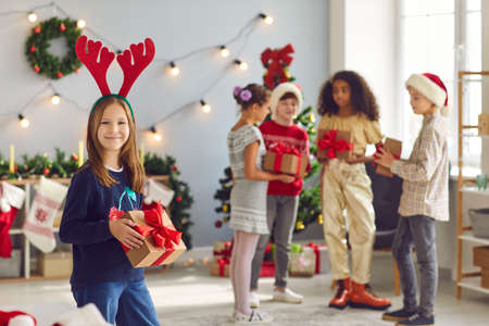 Happy smiling girl in red antlers holding her Christmas present and looking at camera standing against blurred background of cozy living-room with children exchanging gifts Фото со стока