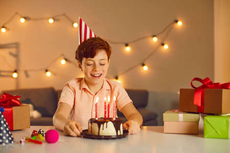 Happy smiling boy in festive cap sitting and looking at birthday holiday cake with candles at home surrounded with present during birthday celebration. Happy birthday at home concept Фото со стока