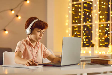 Red haired boy in headphones sitting, looking at laptop and making notes during online lesson, meeting or videocall. Distant education, elearning, gaming at home concept Stock Photo