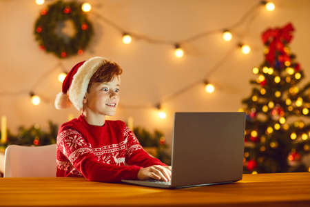 Boy sitting in a room with Christmas decor in front of a laptop with a surprised expression on his face seeing something interesting on the screen. Child spends Christmas Eve at home. Banner concept.