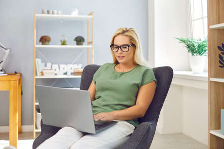 Young blonde woman in glasses working online on notebook at home with room interior at background. Freelance, distant working, online communication, education in internet concept