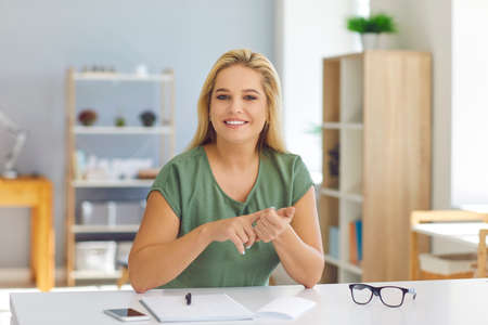 Smiling young woman, tutor, life coach or psychologist, sitting at desk looking at camera, talking to students or clients during online video call, sharing useful tips, giving positive thinking advice Фото со стока