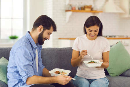 Young couple eating fresh natural healthy takeaway meals from plastic containers together sitting on couch at home. Happy man and woman having lunch they ordered in express food delivery service