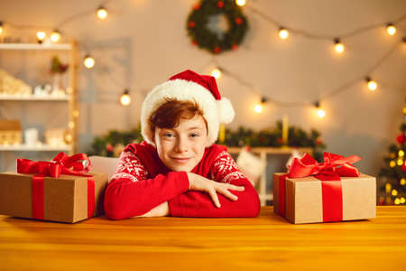 Positive boy in Christmas clothing and hat looking at camera at table surrounded by present boxes over Christmas decorated room at background. Happy children during New Year holidays concept Фото со стока