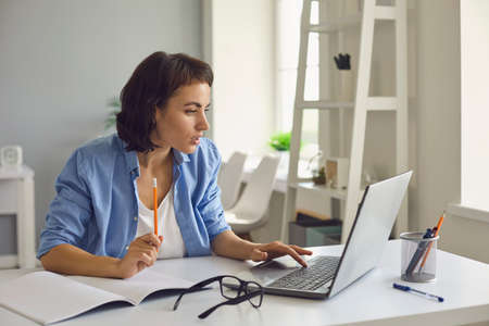 Young woman sitting with laptop and notebook, watching online lesson or videocall and making notes over home interior background. Freelance, elearning and online professions concept
