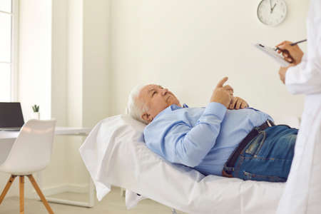 Senior patient lying on bed in hospital office, telling about symptoms, asking questions or clarifying prescription details. Doctor filling out healthcare questionnaire or conducting medical survey