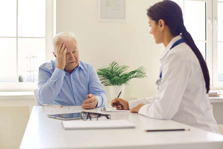 Senior man patient complaining on headache to young positive woman doctor during visit or consultation in moden clinic. Visiting doctor, modern healthcare, mature patients concept Фото со стока
