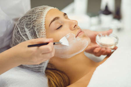 Young woman receiving beauty procedure of applying moisturizing mask with brush from professional beautician in spa salon. Facial skincare in cosmetology