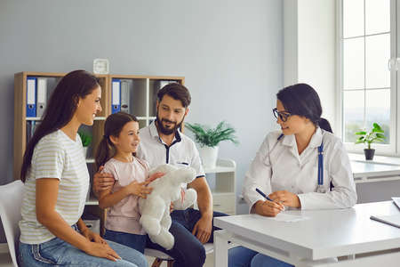 Happy family with child in pediatricians office consulting friendly young female doctor. Mother, father and daughter talking to supportive paediatrician during regular check-up in modern hospital