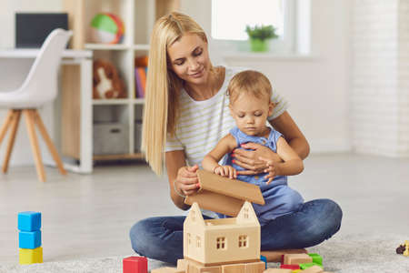 Happy young smiling mother sitting with her small baby boy on knees and building wooden house together at home with room interior at background. Happy childhood and motherhood concept Фото со стока